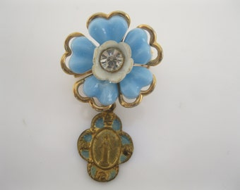Vintage plastic flower with religious medal