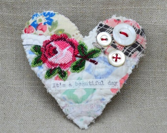 BROOCH Textile heart shaped.  Appliquéd rose trim. Hand stitched. It's a beautiful day