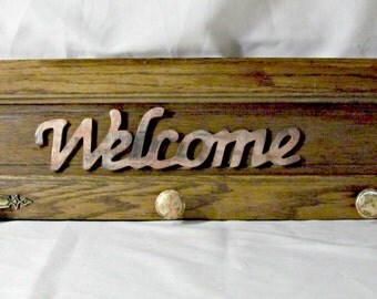 "Rustic ""Welcome"" sign with coat hooks"
