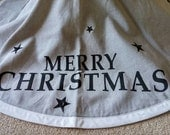 Gray canvas Christmas tree skirt with MERRY CHRISTMAS and black stars