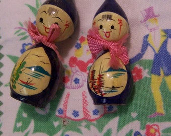 two tiny wooden doll figurines