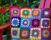 Granny square pillow crocheted in bright cotton yarn