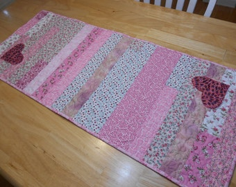 Valentine theme quilted table runner in shades of pink, rose, and mauve