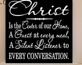 12x 12 wooden sign with vinyl quote: Christ is the center of our home, a guest at every meal, a silent listener to every conversation