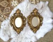 pair faux brass gold ornate glass oval wall mirrors / set of 2