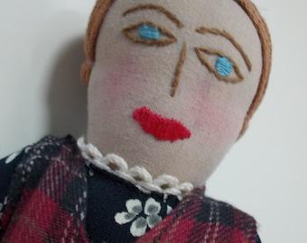 Folk Art Doll Wearing Plaid Apron Over A Black Print Dress