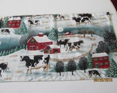 Country Christmas table runner, cows in a snowy barnyard on one side, Santa and reindeer flying thru the night sky on the other.