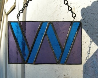 Stained glass W with Wellesley College class colors