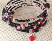 Black and Red Memory Wire Bracelet. Variety of beads. Small bright red heart dangles off end.