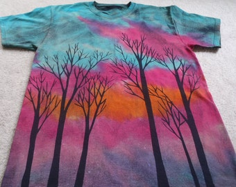Trees, bare branches silhouetted againt a glowing sunset, man's large discharged & dyed t-shirt, colors are intense, oranges, fuchsia, blues