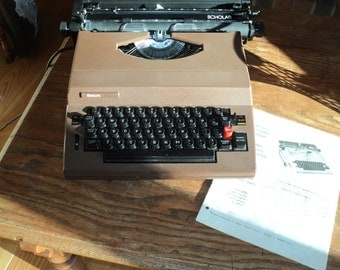 Vintage Electrical Typewriter  with it's own Portable Black Plastic Molded Carrying Case and Owners Manual in Good Working Condition