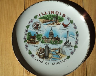 OH BOY!, ILLINOIS Souvenir Plate Transfer Print Decal designed white glazed ceramic wall plate with gold leaf trim in Very Good Condition