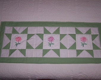 Beautiful table runner. Purple and pink followers on white fabric, Green and white background.
