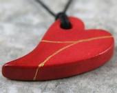 Red faux kintsugi (kintsukuroi) broken heart pendant with gold repair in bisque porcelain on black cotton cord - OOAK