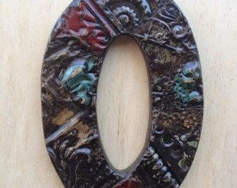 "Patchwork letter ""O"" designed with antique tin ceiling tile"