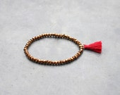 Copper colored bead bracelet with red tassel for women
