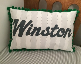 Baby pillow in light gray stripes and slate gray script. Personalized with name.