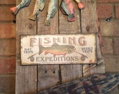 Wooden Fish and Metal Fishing Sign on old Pallet Wood