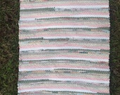 Pretty handwoven rug in soft pinks, greens, and white.