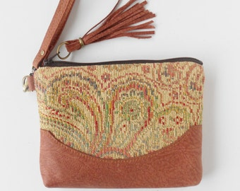 Wristlet or clutch in chenille paisley with leather trim.