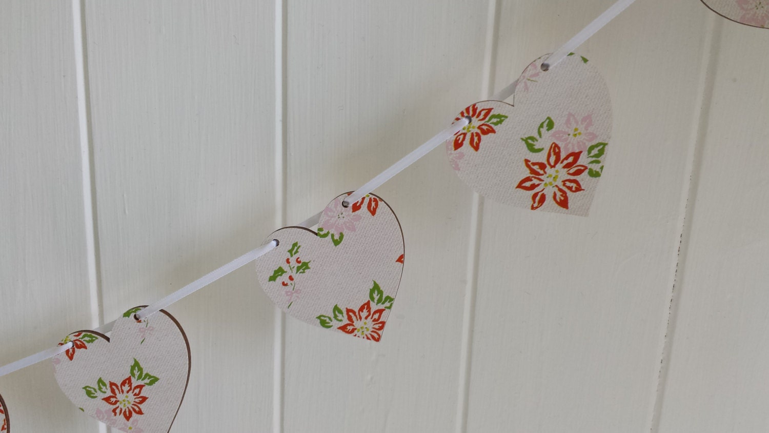 Hand made decoupaged wooden heart Christmas bunting featuring a vintage poinsettia design with a modern feel