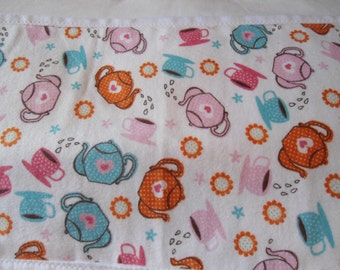 Burp clothes with teapots and cups on white back ground