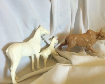 Tan plastic Brahma bull, White horse and foal