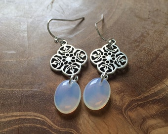 Icedrop - Pair of dangling earrings with decorative, silvertone charm and flat, oval white glass bead which looks like opalite.