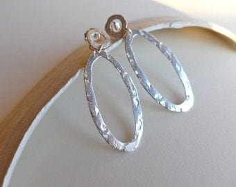 Earring with oval hoop with natural texture.