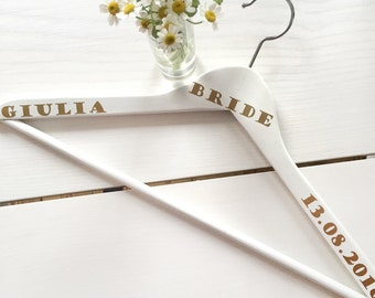White wooden hanger for the wedding dress with wedding date and name of the bride