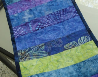 Floral batik table runner. This quilted batik table runner creates a colorful accent.
