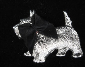 1960's Scottie Dog Brooch- has over-sized black satin bow collar. Brooch is a realistic depiction of this breed. Charming collectible piece!