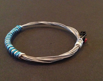 A handmade 4 string recycled guitar string bracelet/bangle