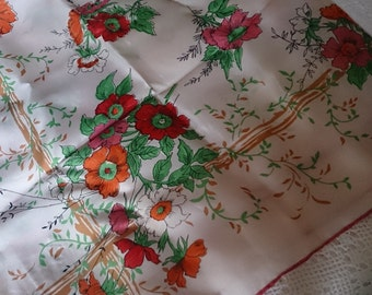 Square rayon scarf with poppies in shades of rust red, orange and pink on an ivory scarf with green trailing foliage.