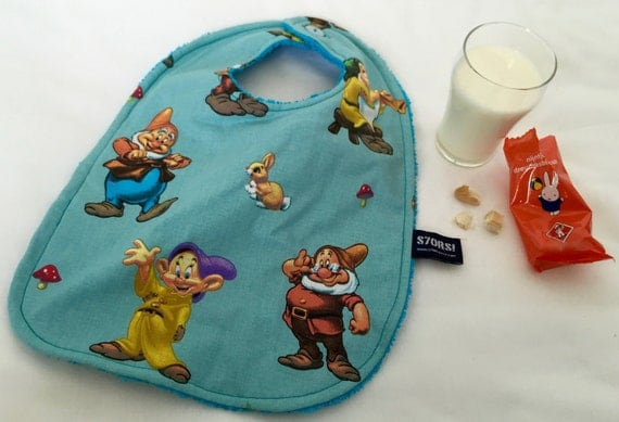 The seven dwarfs, extra-large baby bib. Double sided with two buttons. Ideal for the first bites and baby-led weaning.