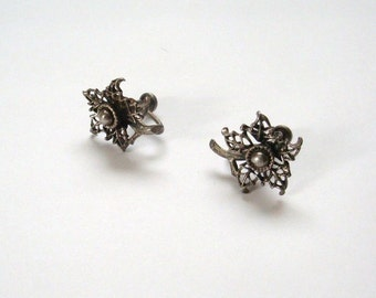 Vintage sterling silver screw back earrings with a floral stem design in very good condition except for some tarnish natural to their age.