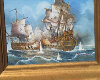 Two galleons in a sea battle;lovely gold wood frame.