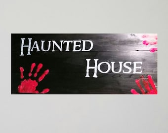 Haunted house with bloody handprints sign