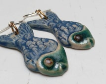 Fish-shaped earrings, hand modeling stoneware. Glazed in blue and green, with silver hook