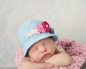 Newborn light blue knit cloche hat with pink flowers and blue trim