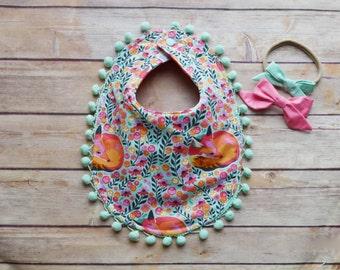 Reversible fox den and pink polka dot mint pom pom baby bib