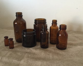 Eight up cycled amber apothecary bottles. Great collection. Vintage / Industrial decor.