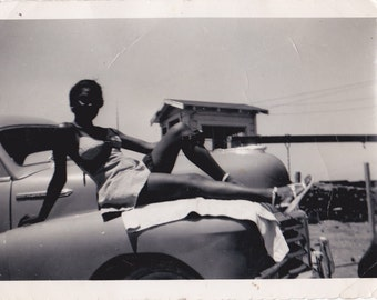 1960s African American Young Lady Sunbathing on Car