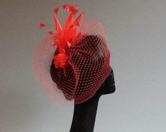 Dutch design fire red fascinator with included but optional birdcage veil on an aliceband