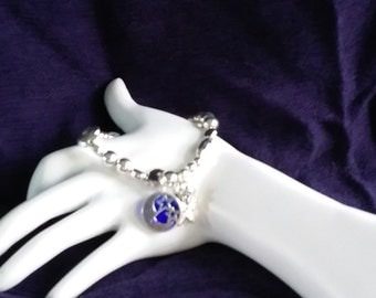 Bracelet has silver beads all around slips on with charms,sun,star, and a sterling silver moon with glass blue back.