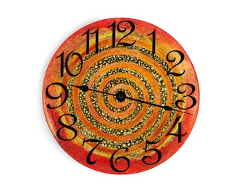 Red wall clock with a rust and speckled swirl in the middle. Circle design.