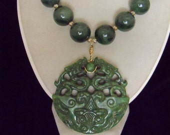 Carved dragon pendant on necklace of large serpentine beads
