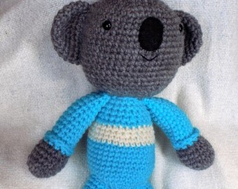 Crocheted amigurumi koala bear in turquoise pajamas