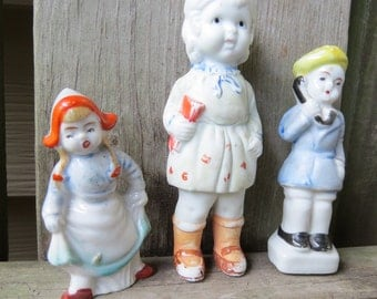3 Antique Bisque Figurines Little school girl, Dutch Girl, Boy with hat on phone  Made in Japan. Child with book figurine