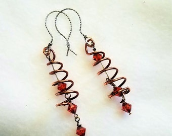 Copper wire coiled around Indian Red Swarovski crystal dangles mounted on sterling silver with sterling hand made earwires.  2 inch drop